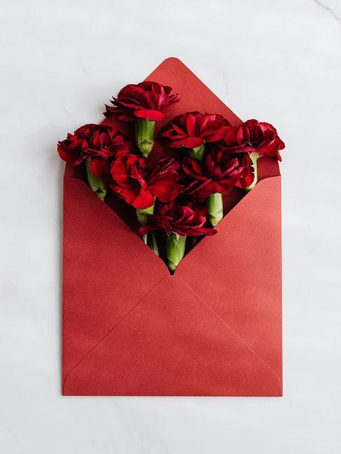kartka na dzień mamy z czerwoną kopertą wypełnioną goździkami