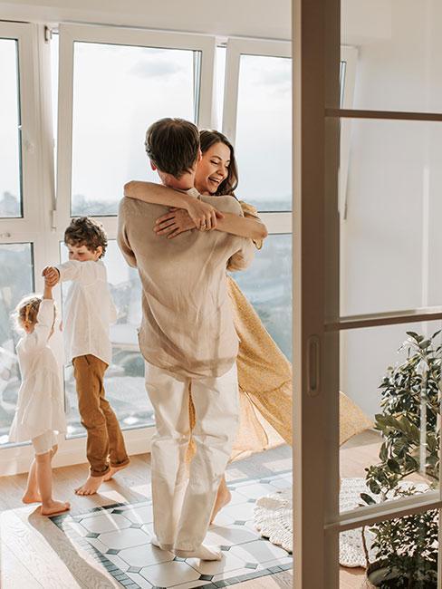 młoda rodzina w jasnych strojach tańcząca w salonie