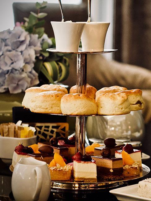 Angielski podwieczorek na etażerce z ciastkami scones i małymi deserami
