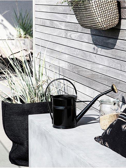 czarna konewka w ogrodzioe przed domem