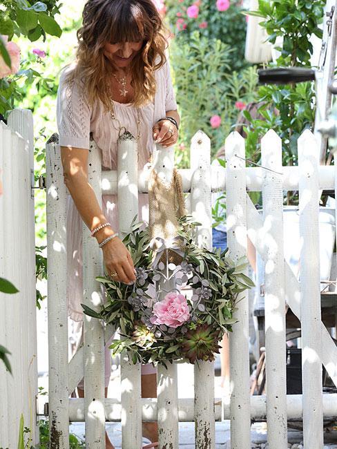 kobiet azawieszająca wieniec na białym płocie w ogrodzie przed domem