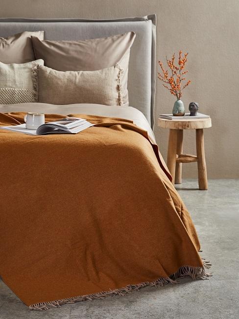 szara sypilania z pomarańczową narzutą i ściana w kolorze greige