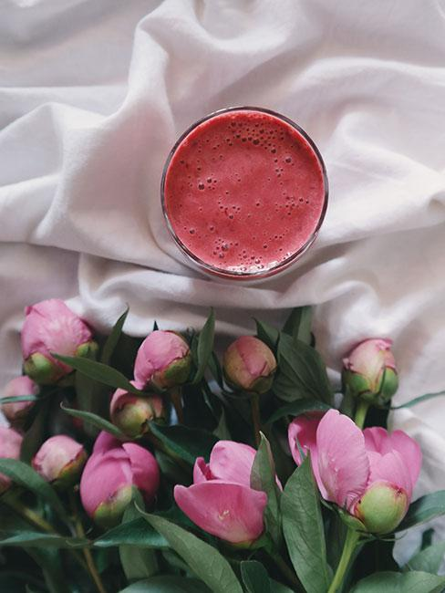 Piwonie w bukiecie obok szklanki ze smoothie