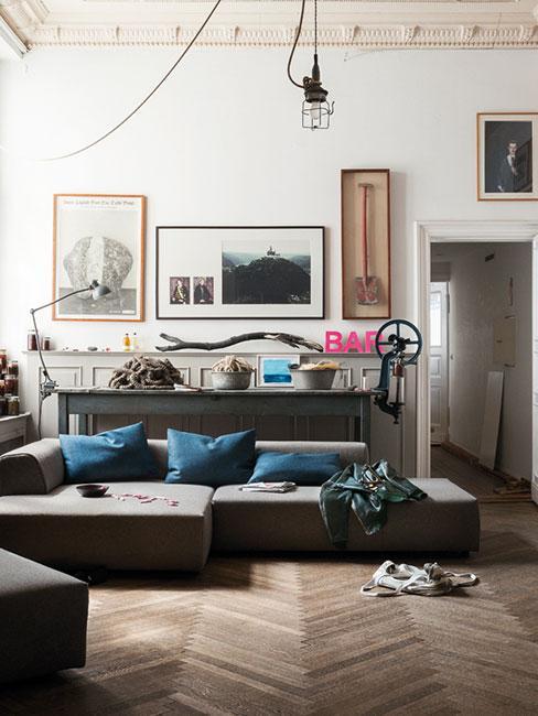 pomysł na ścianę w industrialnym salonie z sofą i obrazami na ścianach