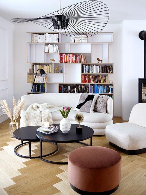 pomysł na ścianę w małym salonie z białą sofą nerką i regałem z książkami