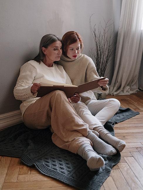 mama i córka przeglądają albym ze zdjęciami na sofie