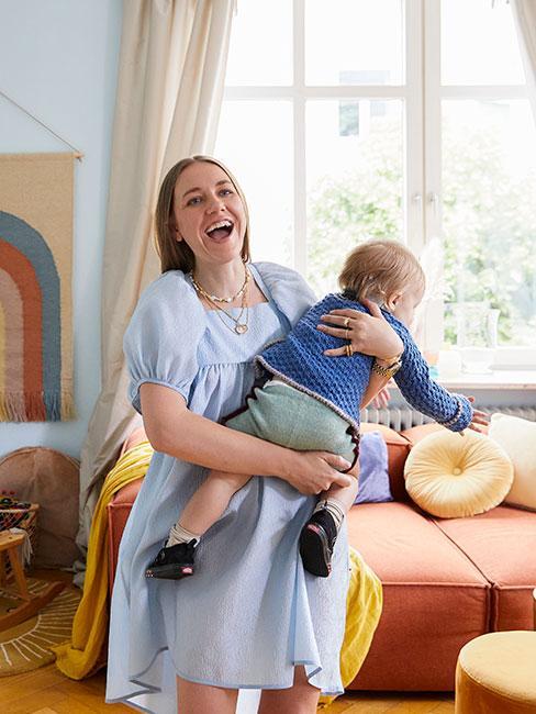 roześmiana młoda kobieta z dzieckiem w kolorowym salonie