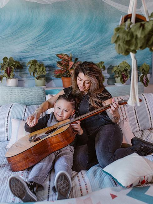 mama z synem ucząca go gry na gitarze