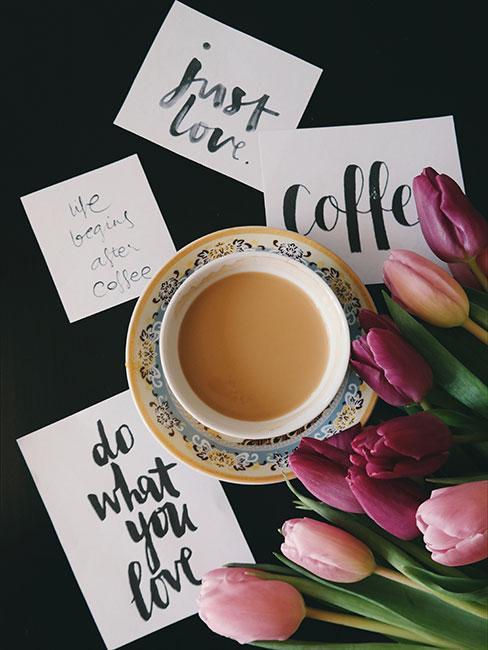 kartki z piękną kaligrafią obok herbaty z mlekiem i tulipanów