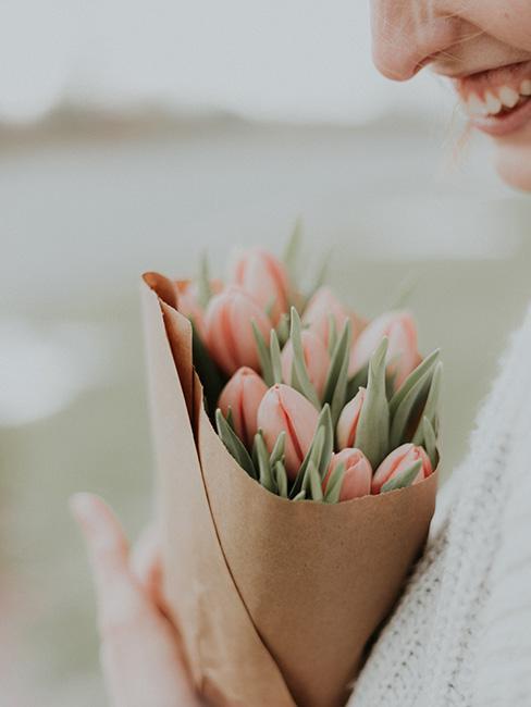 roześmiana kobieta trzymająca bukiet tulipanów