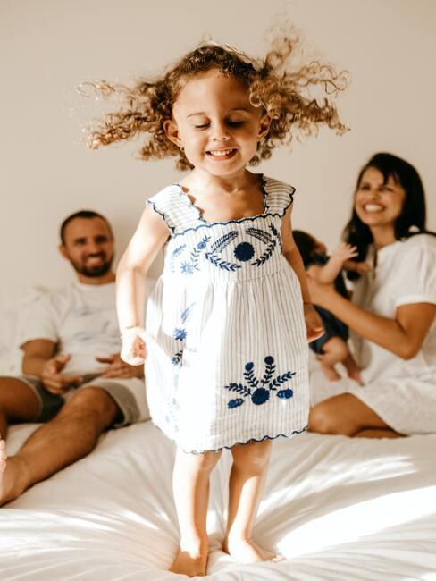 Dziewczynka skacząca z rodzicami
