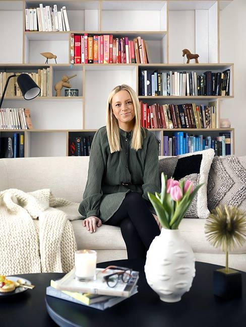 Kobieta siedząca w na fotelu w otoczeniu półek z książkami