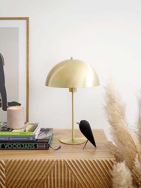 Lampa stojąca na stoliku przy ścianie, obok trawa pampasowa