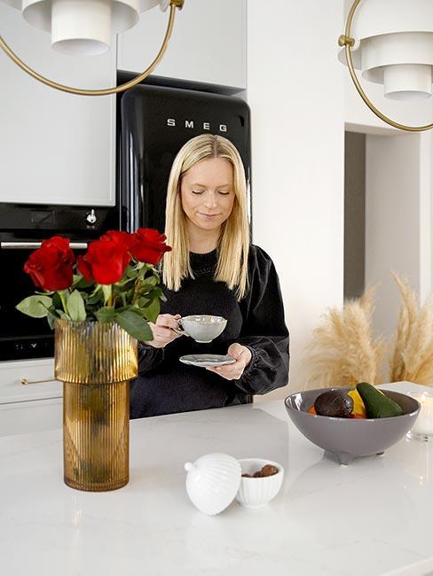 Kobieta stojąca w kuchni z filiżanką kawy
