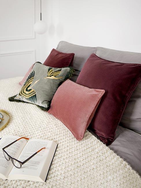Sypialnia z miękką narzutą i poduszkami w odcieniach różu, bordo i oliwkowym