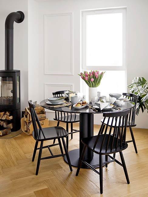 Kącik jadalniany ze stołem i krzesłami, obok kominek