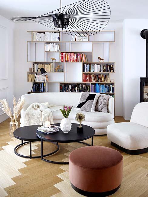 Przestronny salon z drewnianą podłogą i półkami pełnymi książek
