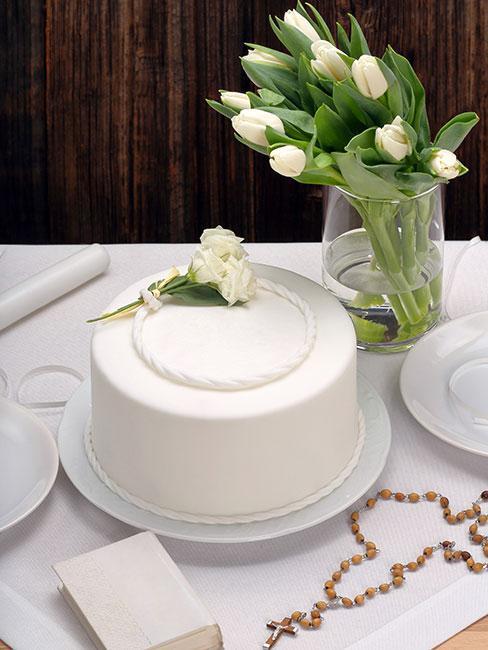 biały tort komunijny obok wazonu z tulipanami