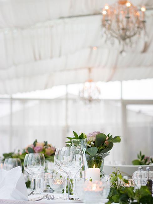 Stół udekorowany odświętnie kwiatami w namiocie weselnym