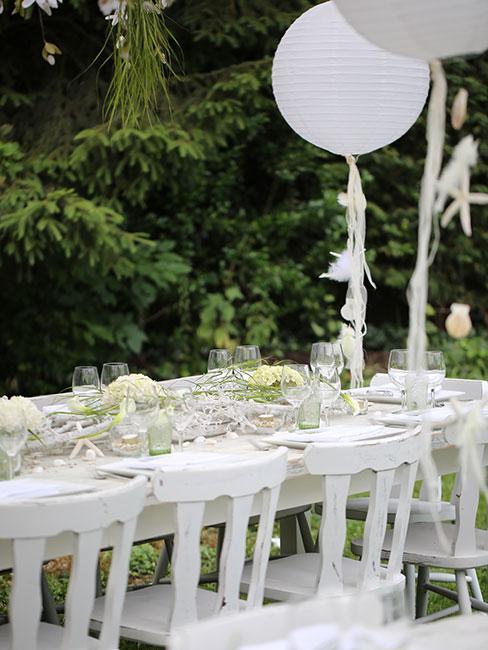 biały stół w ogrodzie z białymi dekoracjami i balonami
