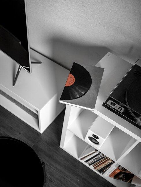 Adapter na białym regale obok notesu z rysunkiem płyty