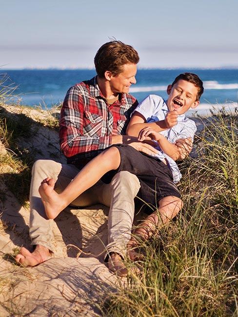 młody roześmiany ojciec z synem na plaży