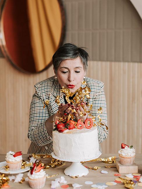 Kobieta zdmuchująca świeczki na 60 urodziny