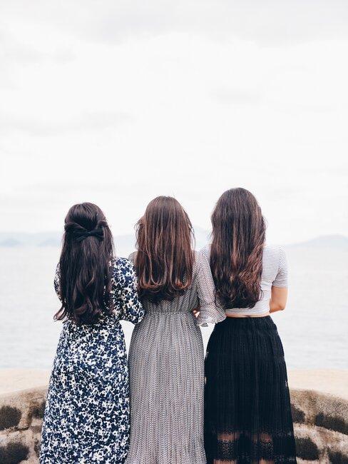 Trzy kobiety w eleganckich sukienkach, odwrócone plecami