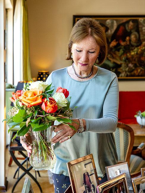 Starsza kobieta układająca kwiaty w wazonie