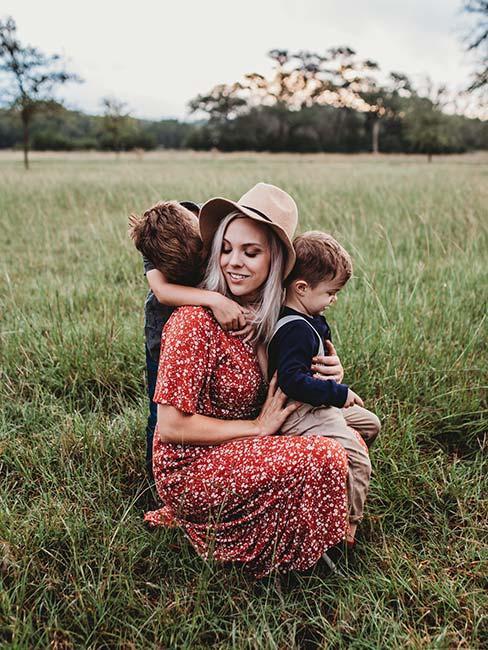 Młoda kobieta z synami na łące