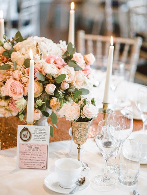 stół z bukietem jasnoróżowych róż zastawiony na komunię z białą zastawą i srebrnymi sztućcami
