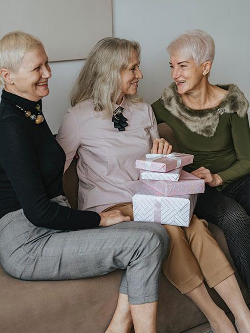 Trzy kobiety siedzące na sofie z prezentami