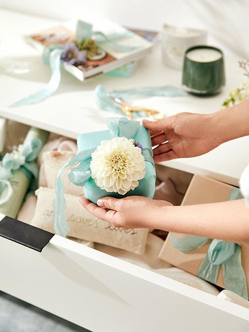 Mały prezent w turkusowy papier i ozdobny kwiat