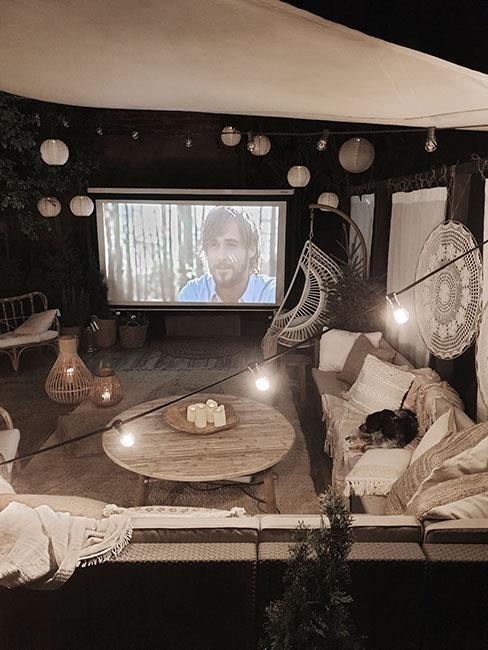 kino w ogrodzie zaaranżowane w stylu boho z lampionami i białymi tekstyliami