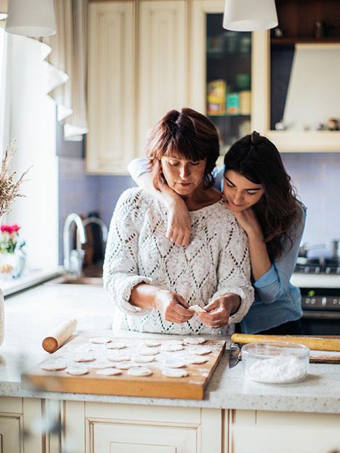 mama z dorosłą córką dekorują ciasteczka w kuchni