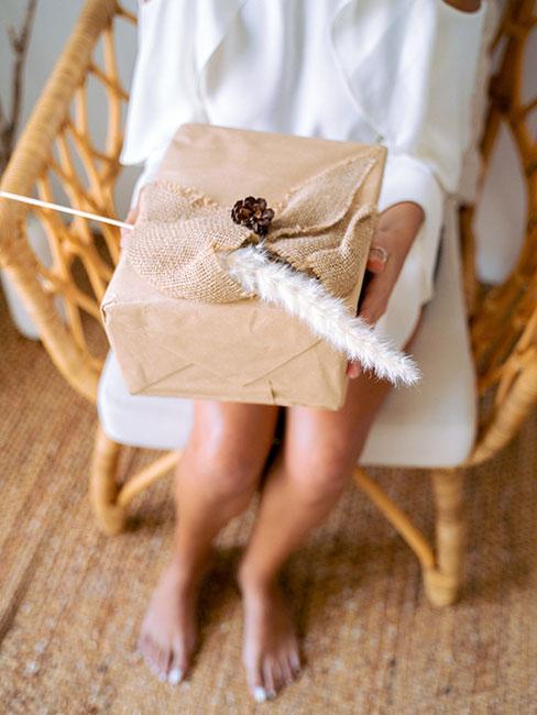 prezent opakowany szarym papierem ozdobiony trawą