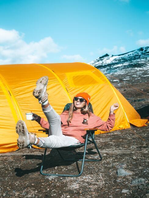 Kobieta siedzi obok żółtego namiotu