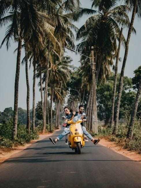 Ludzie jadą motorem obok palm