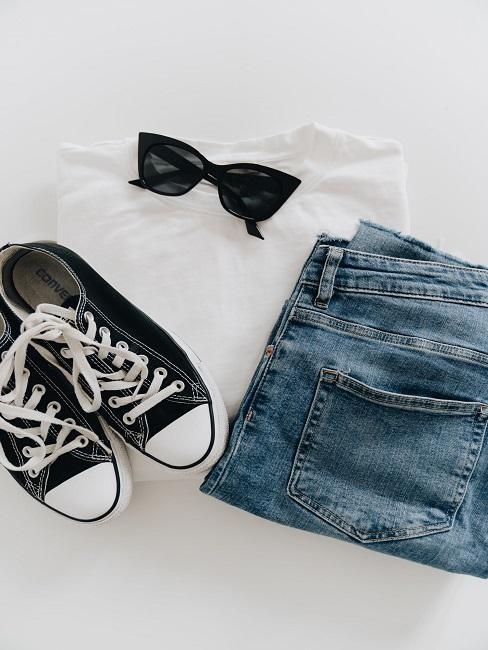 Na białym tle trampki jeansy oraz koszulka i okulary czarne