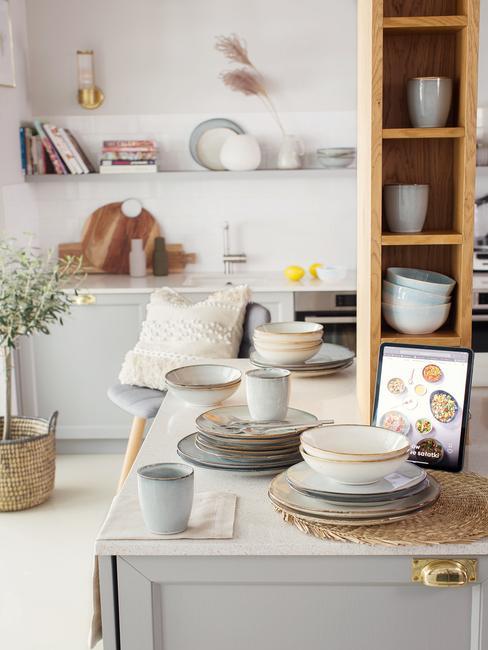 Wnętrze eleganckiej minimalistycznej kuchni, zbliżenie na talerze, szklanki i miseczki