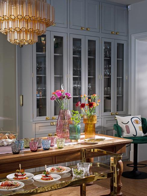 Wnętrze jadalni z dużym żyrandolem , szarymi kredensami i eleganckimi wazonami