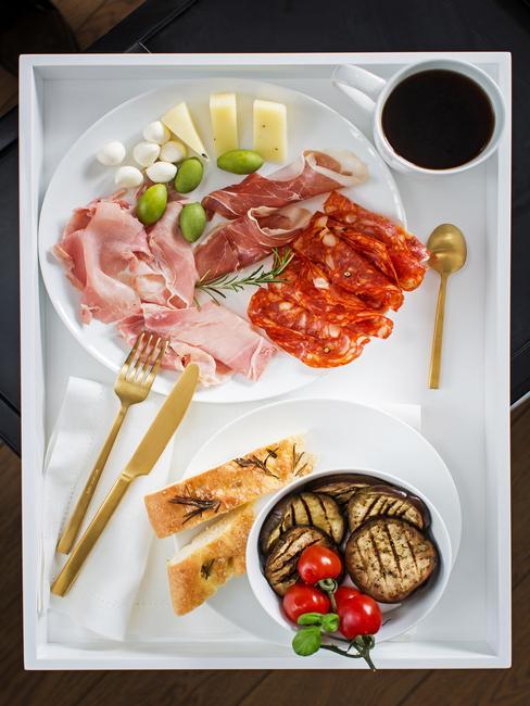 Talerze z jedzniem, wędliny, ser, oliwki, bakłażan