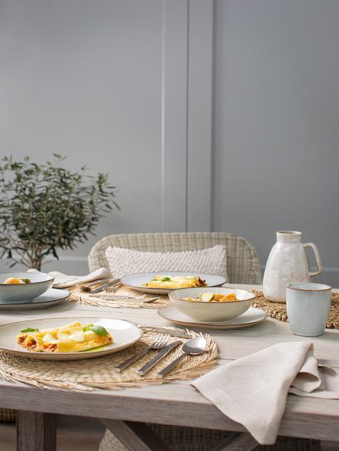 Drewniany stół z naturalnymi dekoracjami i naleśnikami na talerzach