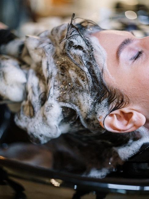 ciemne kobiece włosy myte w salonie fryzjerskim