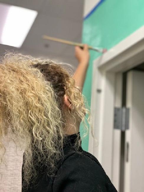 Kobieta z kręconymi włosami maluje ścianę