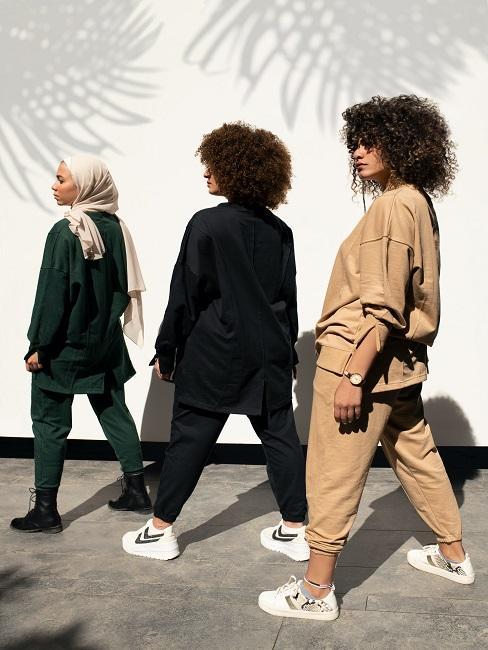 Trzy kobiety stojące na tle białej ściany