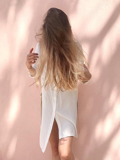 Kobieta w prostych włosach w białej sukience na różowym tle