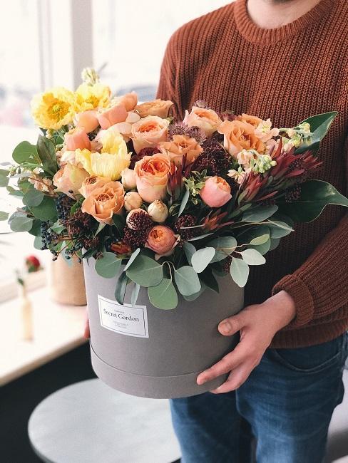 Mężczyzna trzymający pudełko z kwiatami