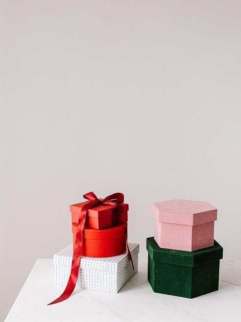 Cztery prezenty na biały stole i beżowym tle