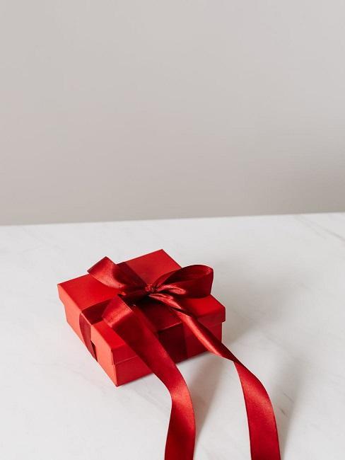 Czerwony prezent na białym stole
